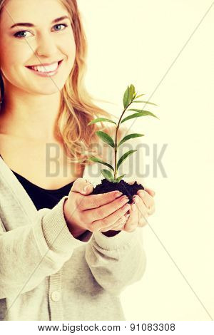Happy woman with plant and dirt in hand