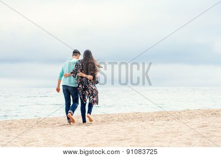 Young Couple Taking A Walk On Beach.