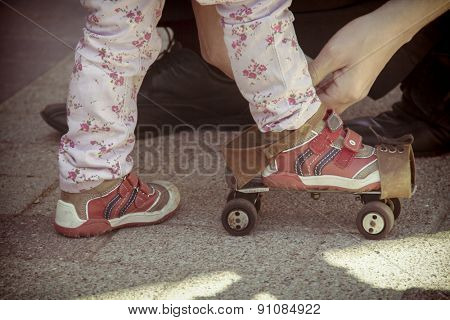 Father helping her little daughter to try on vintage roller skates. Old film photo style.