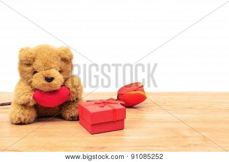 Red Gift Box With Tulip And Teddy Bear On Wooden Table