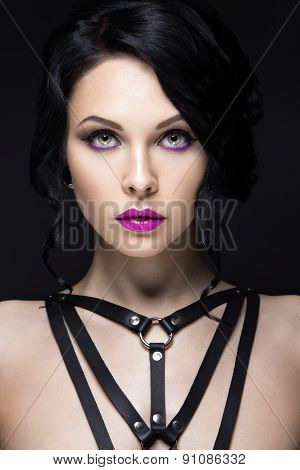 Beautiful Girl in the Gothic style with leather accessories and bright makeup. Beauty face.