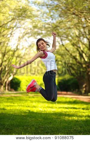 Happy Sportive Girl Jumping In Green Summer Park