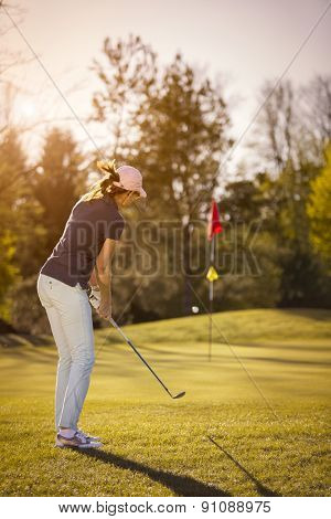 Woman golf player shooting golf ball towards flag at beautiful sunset.