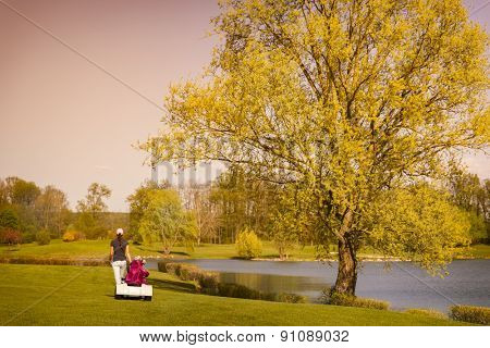 Female golf player walking on fairway with beautiful tree and lake at dusk.