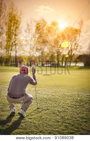 Male golf player crouching to analyze the green at beautiful sunset.