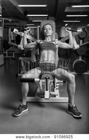 Girl pumps the major muscle groups in the gym.