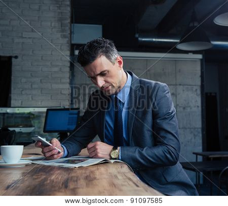 Confident businessman reading magazine and holding smartphone in cafe