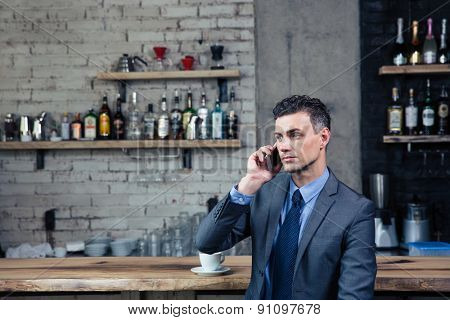 Pensive confident businessman talking on the phone in cafe and looking away
