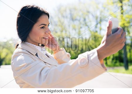Happy woman making selfie photo on smartphone in pak