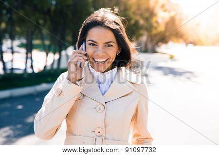 Laughing woman talking on the phone outdoors and looking at camera