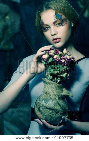 beautiful girl with dry roses in decoration