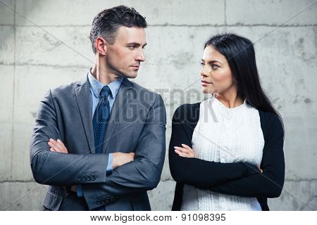Businessman and businesswoman with arms crossed looking at each other over concrete wall