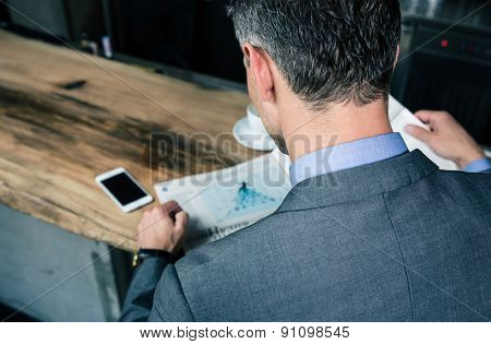 Back view portrait of a businessman reading magazine in cafe