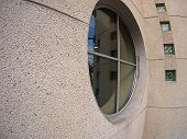 picture of distort  - Detail of a wall of an office building with a round window with wide angle distortion view - JPG