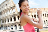 stock photo of suntanning  - Woman applying sunscreen suntan lotion on travel in Rome by the Colosseum - JPG