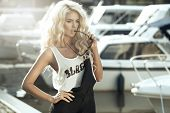 stock photo of dungarees  - Stylish woman in dungarees standing on marina - JPG