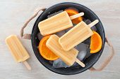 image of popsicle  - Homemade orange yogurt popsicles in a rustic ice filled tin pail with fresh fruit slices - JPG
