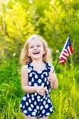 stock photo of laugh  - Laughing blond little girl with long curly hair holding american flag outdoor portrait on sunny day in summer park - JPG