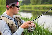 pic of fisherman  - Fisherman on the river bank in sunglasses - JPG
