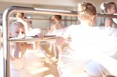 stock photo of ballet barre  - Little White Ballerinas Doing a Stretching Exercise Using a Ballet Horizontal Bar at the Dance Studio - JPG