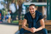stock photo of sitting a bench  - Handsome smiling and casual young man sitting on bench - JPG