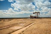 stock photo of oilfield  - Tire prints leading to oil pump jack - JPG