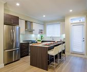 stock photo of home addition  - Modern kitchen interior with island and cabinets in a luxury house - JPG