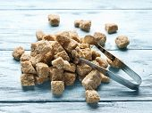 foto of sugar cube  - Cubes of cane sugar on blue wooden table - JPG