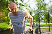stock photo of vest  - Young man in grey vest training on sport equipment outside - JPG