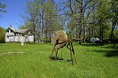stock photo of abandoned house  - An old grinding wheel full of rust is located in the yard of an abandoned house - JPG