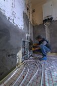 foto of convection  - pipefitter installing system of heating - JPG