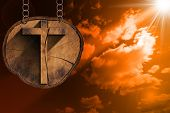 foto of cross-section  - Wooden Christian cross on a section of tree trunk hanging from a metal chain at the beautiful sunset with clouds - JPG