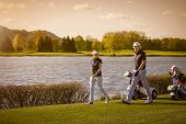 foto of golf bag  - Golf player couple walking on fairway with beautiful lake in background at sunset - JPG