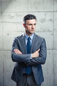 foto of thoughtfulness  - Portrait of a thoughtful businessman standing with arms folded over concrete wall and looking away - JPG