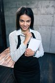 image of waiter  - Smiling beautiful female waiter in apron standing with notepad and pen in cafe - JPG