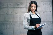 foto of waiter  - Happy cute female waiter in apron with notepad and pen in cafe - JPG