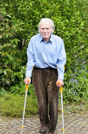 stock photo of crutch  - Elderly man with casual clothes using forearm crutches as a mobility aid to walk on the cobblestones of a footpath in a green park or yard full length - JPG