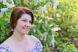 image of denude  - An adult woman near blossoming bird cherry in the park - JPG