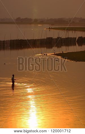 Silhouetted people on U Bein Bridge at sunset, Amarapura, Mandalay , Myanmar