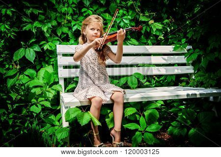 Pretty little girl playing the violin at a summer park.