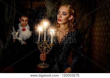 Bloodthirsty male vampire in medieval dress is going to bite a beautiful lady. Halloween.