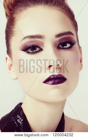 Vintage style close-up portrait of young beautiful girl with winged eyes make-up and dark lipstick