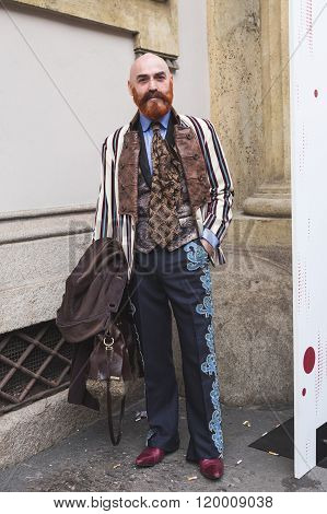 MILAN ITALY - FEBRUARY 25: Fashionable man poses outside Luisa Beccaria fashion show building for Milan Women's Fashion Week on FEBRUARY 25, 2016 in Milan.
