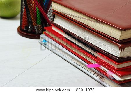 Group of school supplies, books, diaries, on a wooden table surfase. close-up photo
