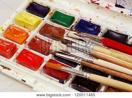 Bright watercolor paints and used brushes for painting. close-up.