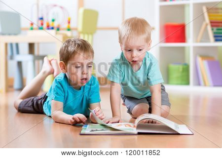 happy kids boys brothers reading encyclopedia together at home