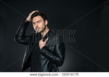 Brutal man smoking on the black background