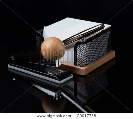 wooden stationery set with silver pen isolated on a dark background