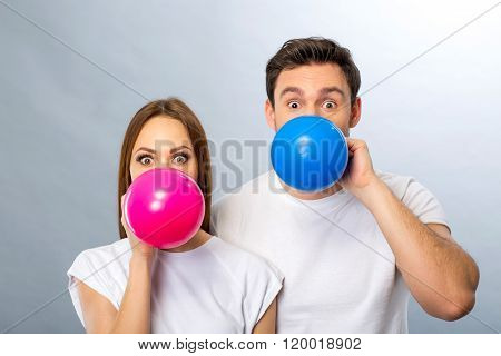Cheerful young couple blowing balloons
