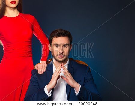 Handsome man sitting in the armchair  near attractive woman